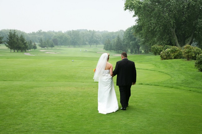 Wedding couple walking at a golf course.