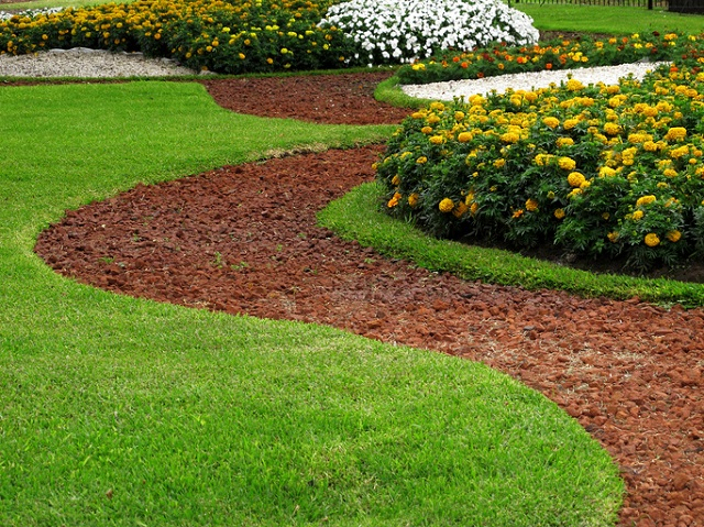 Park design stone pathways in grass with flower beds