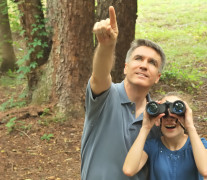 Older male and Girl bird watching in woods.